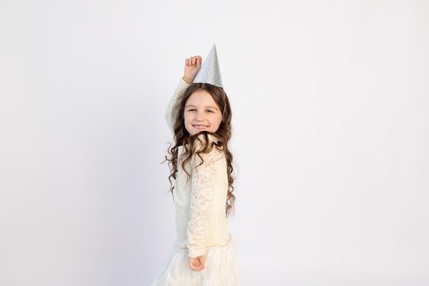 Een schattig klein meisje met een pet op een witte achtergrond geïsoleerd is dansen en verheugt zich. ruimte voor tekst