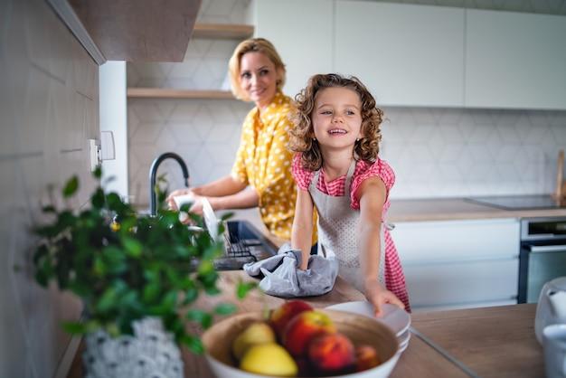 Een schattig klein meisje met moeder binnenshuis in de keuken thuis, de afwas doen.