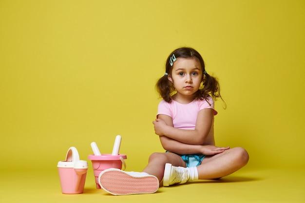 Een schattig klein meisje met paardenstaarten zittend in zomerkleding met strandspeelgoed een emmer, een gieter en een hark met een schop. geïsoleerd op geel met kopie ruimte