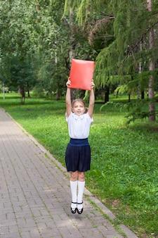 Een schattig klein meisje met twee staarten houdt een map met papieren in haar handen. wandelen in het park, terug naar school