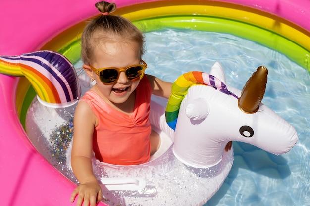 Een schattig klein meisje met zonnebril zwemt met een eenhoornvormige reddingsboei in een opblaasbaar zwembad