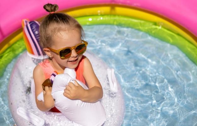 Een schattig klein meisje met zonnebril zwemt met een reddingsboei in een klein opblaasbaar zwembad