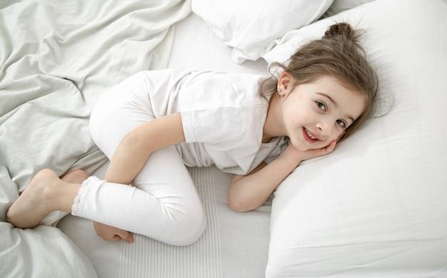 Een schattig klein meisje slaapt in een wit bed. concept van de ontwikkeling en slaap van het kind.