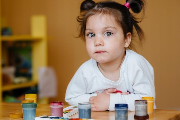 Een schattig klein meisje speelt en schildert in haar kamer. recreatie en amusement.