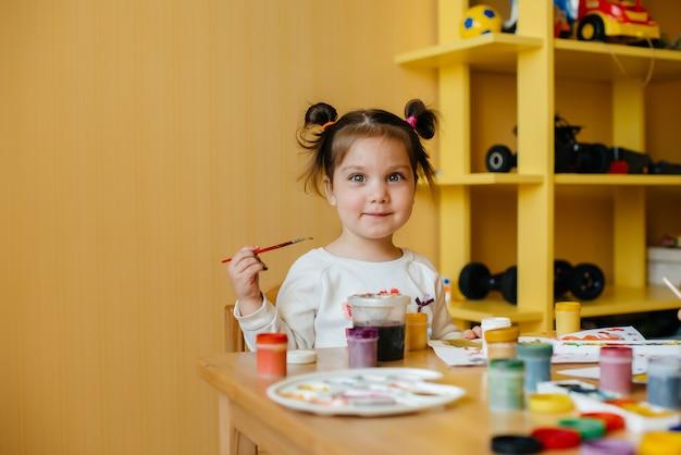 Een schattig klein meisje speelt en schildert in haar kamer