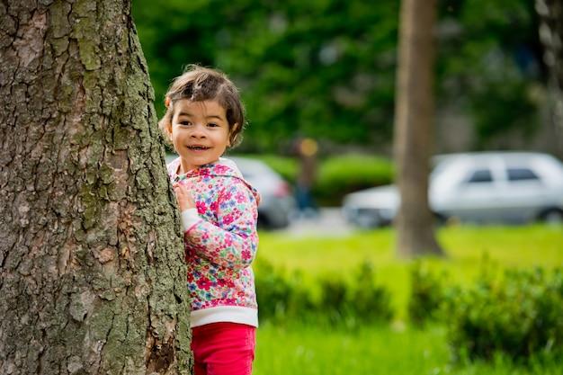 Een schattig klein meisje staat bij de boom in het park en lacht