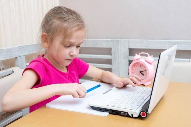 Een schattig klein meisje zit aan een tafel en typt huiswerk op een laptop om ter beoordeling naar de leraar te sturen