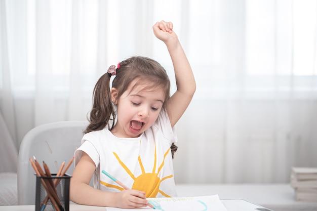 Een schattig klein meisje zit aan tafel en doet haar huiswerk. thuisonderwijs en onderwijsconcept.