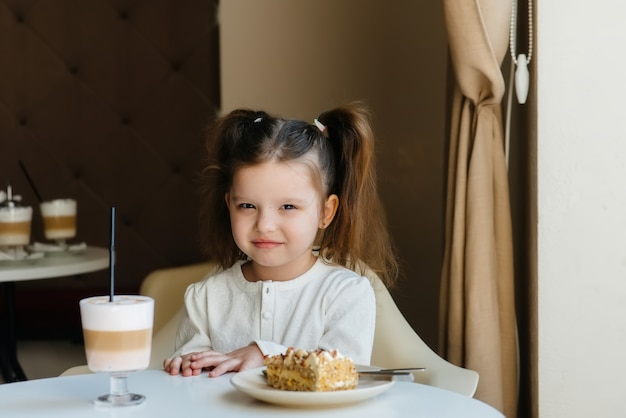Een schattig klein meisje zit in een café en kijkt naar een close-up van cake en cacao. dieet en goede voeding.