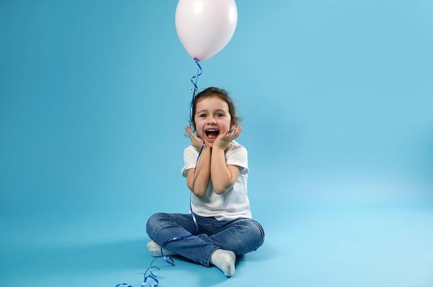Een schattig klein meisje zit op een blauwe ondergrond met een ballon in haar handen en verheugt zich over de verrassing van haar verjaardag expressie van vreugdevolle emoties