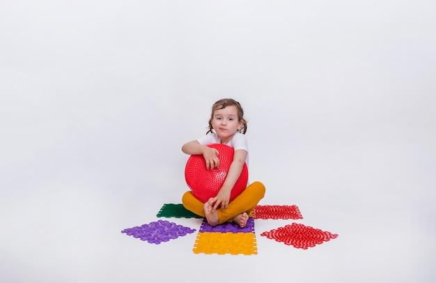 Een schattig klein meisje zit op een kleurrijke orthopedische mat met een rood evenwichtskussen. preventie van platvoeten