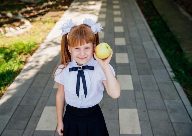 Een schattig klein schoolmeisje staat in het park of op het schoolplein en houdt een groene appel in haar handen.