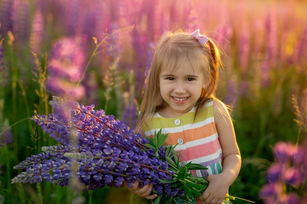 Een schattig klein vrolijk meisje met een boeket lupines in een veld met paarse bloemen bij zonsondergang