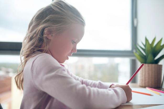 Een schattig meisje dat aan tafel zit te tekenen
