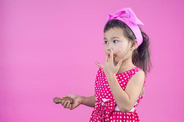 Een schattig meisje dat een rood gestreept shirt draagt dat een chocolade eet met een vuile mond op het roze.