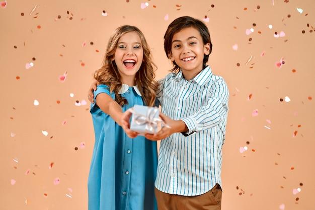 Een schattig meisje in een blauwe jurk en een leuke jongen strekken een doos uit met een cadeau voor de camera, valentijn hartjes confetti valt bovenop hen geïsoleerd