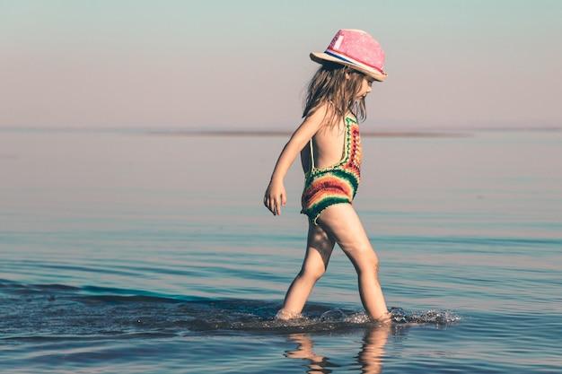 Een schattig meisje in een gebreid zwempak en een roze hoed loopt in ondiep water langs de kust