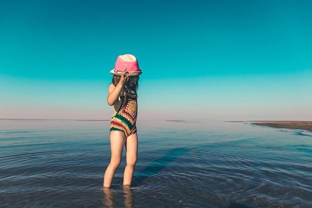 Een schattig meisje in een gebreid zwempak en een roze hoed staat in de zee bij de kust kopieer de ruimte