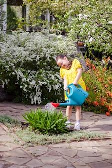 Een schattig meisje in een gele jurk geeft bloemen water uit een blauwe gieter en sprenkelt waterdruppels in...