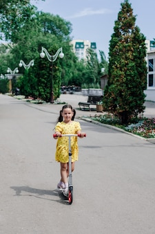 Een schattig meisje in een gele zomerjurk leert op een scooter door de stad rijden en geniet van een warme zomerdag