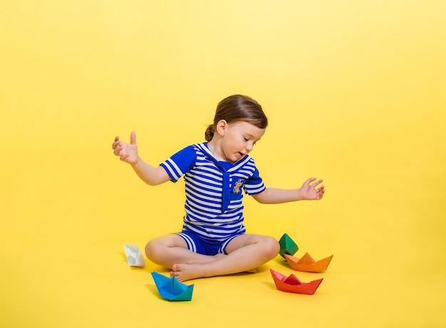 Een schattig meisje in een matrozenpak kijkt verbaasd naar de papieren boten op een gele ruimte. verticale oriëntatie. een mooi klein meisje spreidt haar handen en kijkt naar de kleurrijke papieren boten.