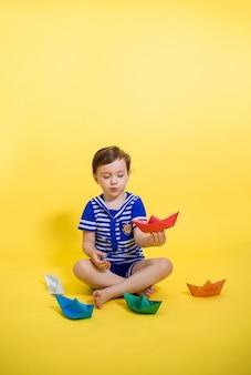 Een schattig meisje in een matrozenpak speelt met papieren boten op een gele ruimte. verticale oriëntatie.