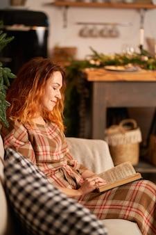 Een schattig meisje leest een boek in een warme en gezellige sfeer. ontspanning en privacy concept.
