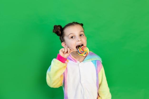 Een schattig meisje likt een grote lolly in een licht pak op een geïsoleerde groene achtergrond. ruimte voor tekst.