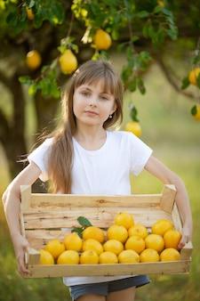 Een schattig meisje met blond haar in een wit t-shirt met zomercitroenen in de tuin onder een boom