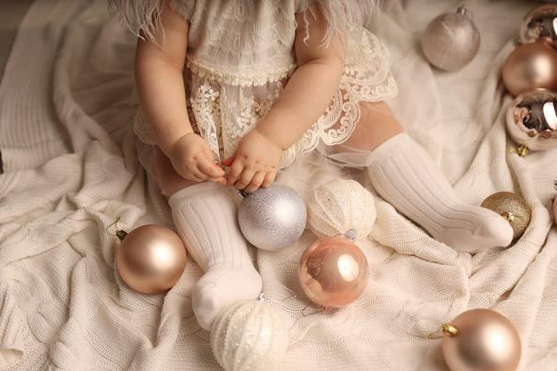 Een schattig meisje met een donkere huidskleur zit op een witte gebreide deken en speelt met kerstboomspeelgoed