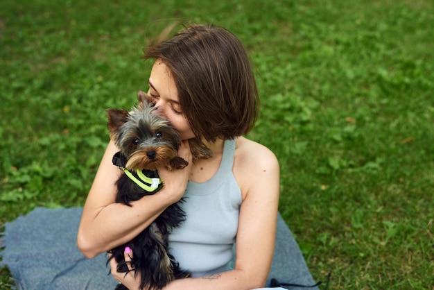 Een schattig meisje met een vierkant omhelst een yorkshire terriër op straat. knuffels met kleine hond