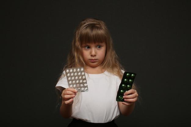 Een schattig meisje met lang blond haar houdt pillen in haar handen en kijkt ernaar.
