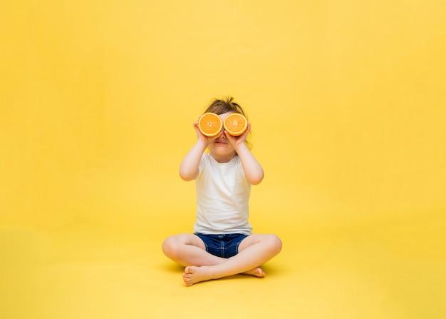 Een schattig meisje zit en houdt de helften sinaasappelen voor haar ogen. een klein meisje zit in kleermakerszit. een klein meisje in een wit t-shirt en denim shorts op een gele ruimte.