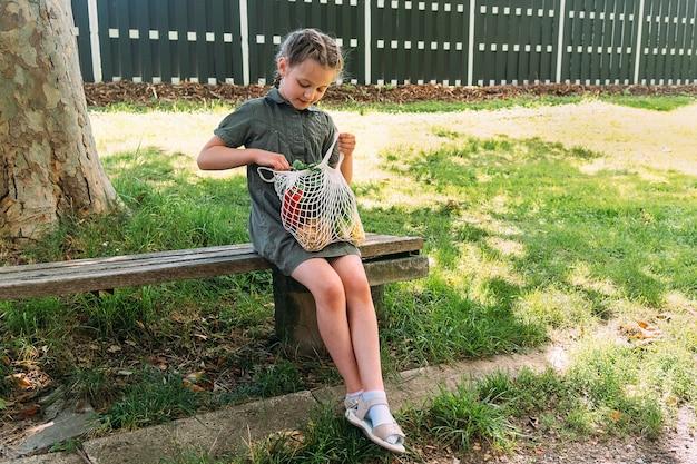 Een schattig meisje zit op een bankje in de natuur met een katoenen koordzak met groenten