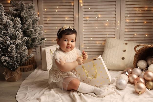 Een schattig meisje zit op een gebreide deken en speelt met een pakket cadeaus voor het nieuwe jaar
