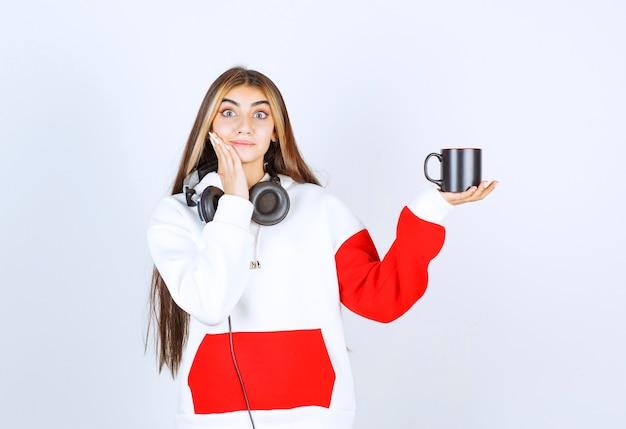 Een schattig meisjesmodel dat in een koptelefoon staat en een kopje drank vasthoudt