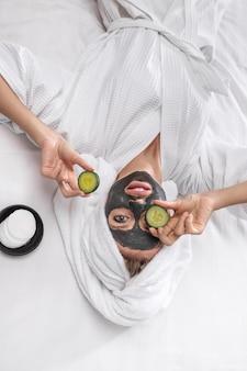 Een schattig model poseert in een witte badjas en een handdoek op haar hoofd met twee plakjes komkommers in de ene hand en de andere op het oog, met wattenschijfjes op het hoofd. opzoeken.