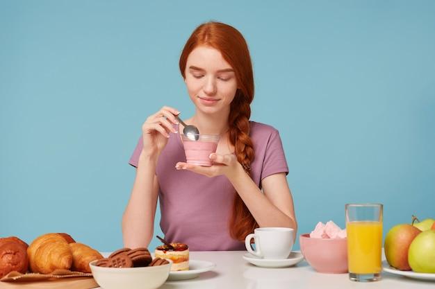 Een schattig roodharig meisje met een vlecht zit aan een tafel, heeft lunch, houdt in haar handen een kersenyoghurt
