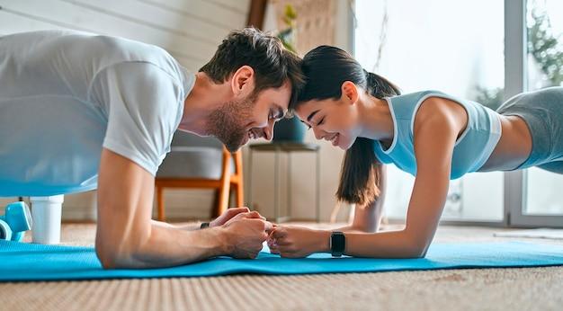 Een schattig stel in sportkleding doet thuis een oefenplank op de matten in de woonkamer. gezonde levensstijl, sport, yoga, fitness.