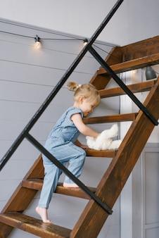 Een schattig tweejarig meisje in een spijkerbroek met een knuffel in haar handen klimt de trap op