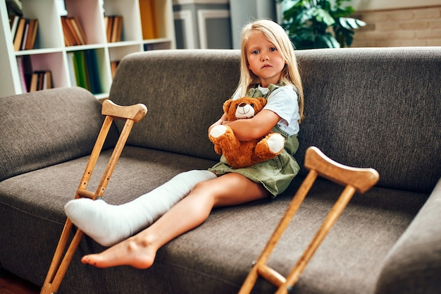 Een schattig verdrietig meisje met een gebroken been in het gips, zit op de bank en knuffelt een teddybeer thuis. er zijn krukken bij de bank voor een snelle revalidatie.