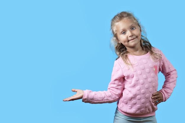 Een schattig vrolijk meisje met kuiltjes op haar wangen en krullend haar glimlacht op blauw