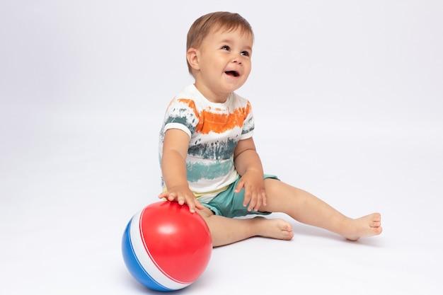 Een schattige afbeelding van een baby die een bal vasthoudt. afbeelding is geïsoleerd op een witte achtergrond