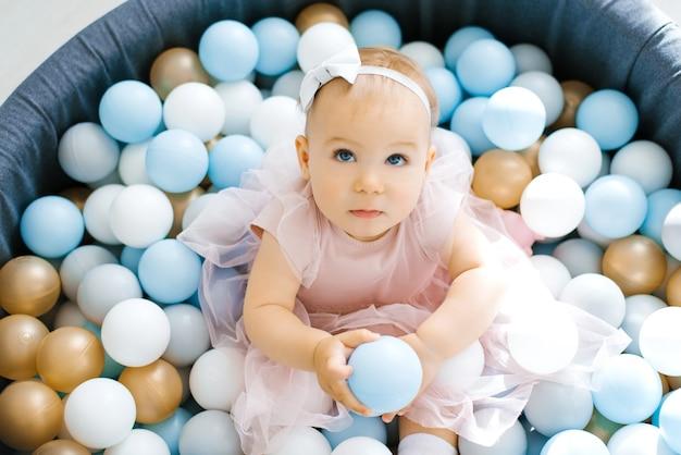 Een schattige baby in een roze jurk baadt in een speelgoedzwembad met ballonnen