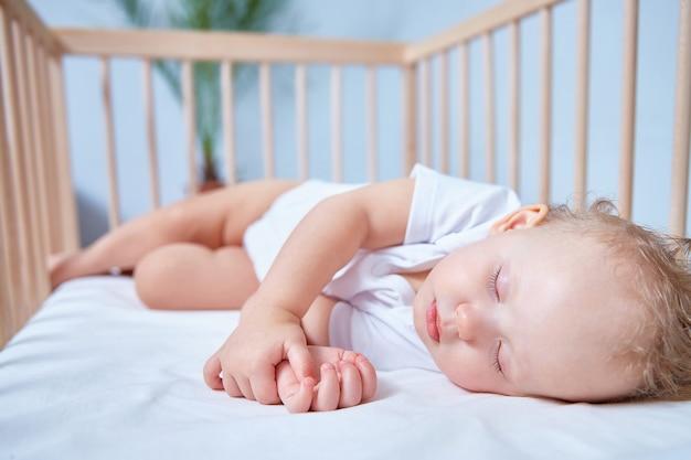 Een schattige baby in witte kleren slaapt in een houten wieg in een helder