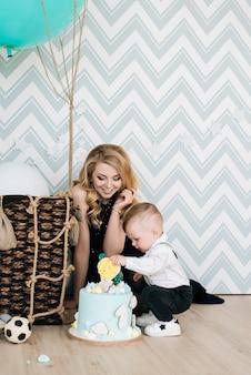 Een schattige baby speelt met zijn jonge moeder op zijn eerste verjaardag. het concept van een kinderfeestje met ballonnen