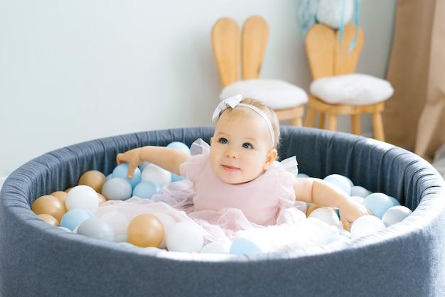 Een schattige baby van één jaar in een roze jurk is aan het baden in een speelgoedzwembad met gekleurde ballen en glimlacht
