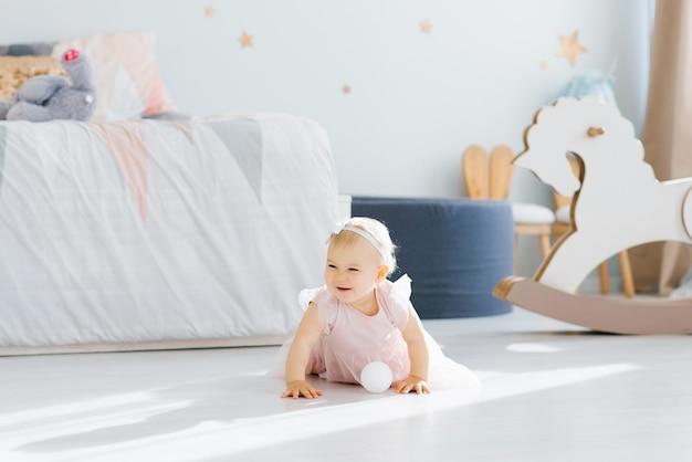 Een schattige blonde baby van een jaar oud in een roze jurk houdt kruipend op zijn handen
