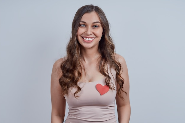 Een schattige blonde in een roze t-shirt, met een rood hartsymbool op haar borst, glimlachend, kijkend naar de camera. studio opname. fijne valentijnsdag, wereldhartdag.