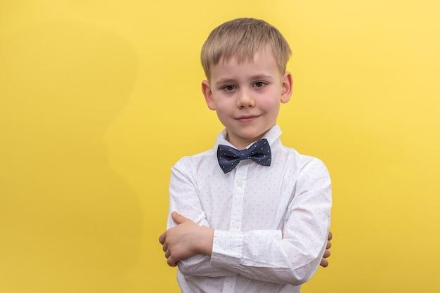 Een schattige blonde jongen in een overhemd en vlinderdas staat met zijn armen gekruist op geel